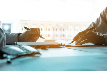 Two young businessman holding pen pointing at the earnings profit and analyze together on desk in company room office. Stock Photo
