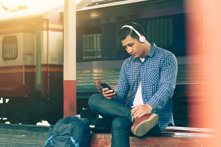 Asian young man using smartphone and listen music waiting train at train station.