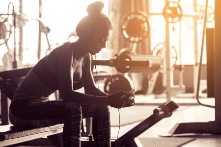 Mujer saludable relajarse después del ejercicio y la canción de búsqueda con escuchar música después del entrenamiento. Foto de archivo