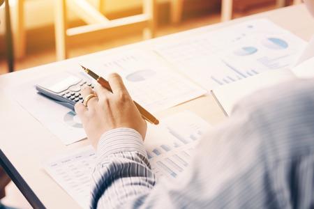 Vista trasera del hombre asiático de negocios calcular con el informe de resumen de resultado de análisis sobre el escritorio en la sala de la oficina de la empresa. Foto de archivo - 84157600
