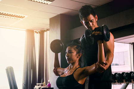 Personal trainer helping woman working lift heavy dumbbells two hand top a head.