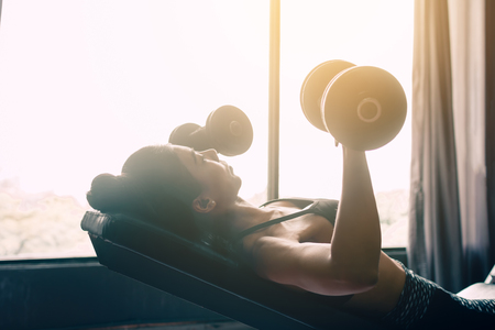 Beautiful asian woman lifting weights dumbbell for her chest near window at gym inside.