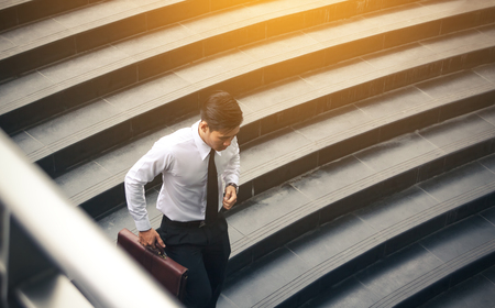 Young asian businessman holding briefcase and running to meeting at underground office building.