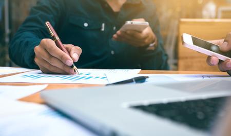 Hombre de negocios escribiendo o apuntando resumen informe gráfico y el uso de teléfonos inteligentes buscando datos. Foto de archivo