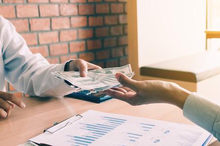 Empresario de mano dando dinero en efectivo de dólares a mano hombre con concepto de corrupción. Foto de archivo