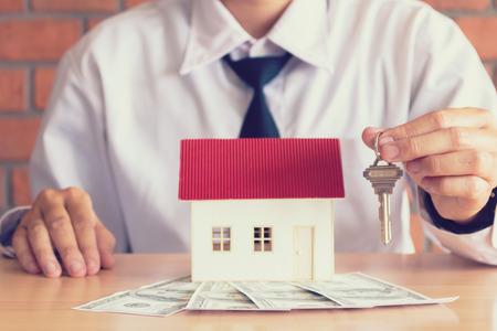 Corredores de casa de vendedor de la llave de la explotación a nuevo cliente de los dueños de una casa. Foto de archivo