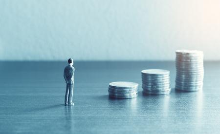 Las personas en miniatura de pie con la pila de apuntar monedas sobre el concepto de ahorro de dinero financiero y futuro.