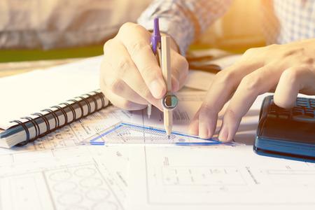 Hombre del ingeniero del arquitecto calcular el área del edificio con el equipo en el escritorio en la oficina en el país.