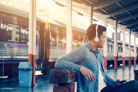 Apuesto joven asiático escuchar música en smartphone con waitting tren en la estación. Foto de archivo