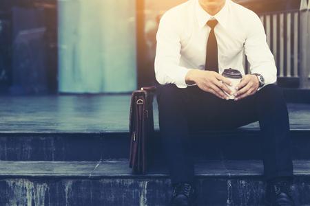 Hombre de negocios sentado delante del edificio de la empresa con el concepto de esperanza.