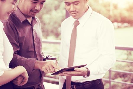 Grupo empresarial de Asia hablando de resultado y buscando datos en tableta.