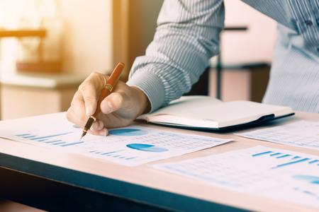 Empresario apuntando la pluma en el gráfico de papeleo gráfico de informe de resumen sobre el escritorio para analizar los ingresos de datos en la oficina en casa. Foto de archivo
