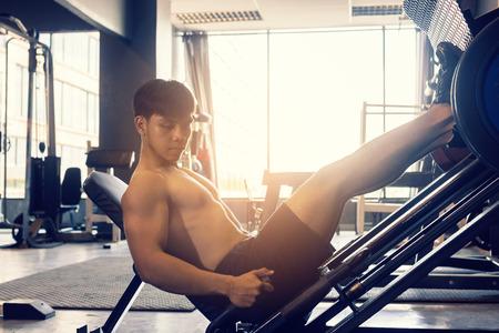 Deportivo hombre joven asiático trabajar el trabajo pesado en el gimnasio de la máquina de la prensa de la pierna de interior. Foto de archivo