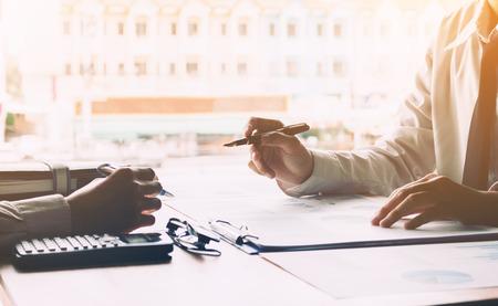 Dos personal asiático de negocios de enseñanza y formación para el compañero en la empresa con calcular el resultado de los resultados de examen sobre el papeleo en la sala de la oficina.