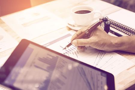 Hombre de negocios de la mano apuntando en informe de gráfico de resumen y sosteniendo la tableta para buscar información de datos.