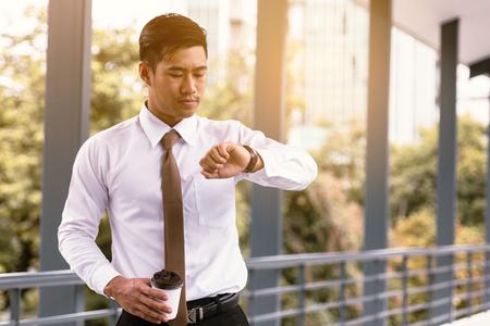 Joven, asiático, macho, posición, comprobación, tiempo, tenencia, café, taza, confiado, Mirar, relojes, mano, afuera, empresa. Foto de archivo