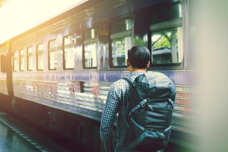 Detrás del hombre joven asiático que se coloca y que espera el tren en la plataforma.
