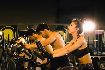 Grupo de tres personas en bicicleta en el interior del gimnasio con ejercicios de entrenamiento cardiovascular.