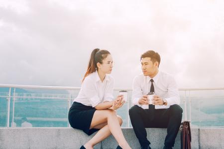 Dos hombres de negocios asiáticos hablando fuera de la empresa con la celebración de café y romper el concepto de tiempo de descanso. Foto de archivo