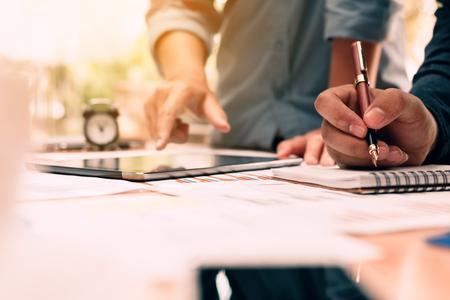 Cerrar la escritura del hombre de mano escribir nota en el bloc de notas y la mano apuntando con el uso de tableta en el escritorio en la sala de la oficina. Foto de archivo