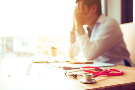 Close up estetoscopio y asiático médico sentado con portátil con dolor de cabeza por estrés.