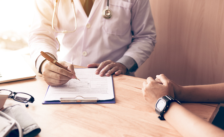 Doctor hand holding pen writing patient history list on note pad and talking to the patient about medication and treatment.