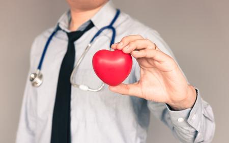 Doctor con el desgaste ocasional y la mano que sostiene el corazón.