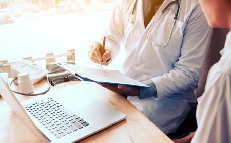 Asiático, masculino, doctor, mano, tenencia, pluma, escritura, paciente, historia, lista, nota, almohadilla, computador portatil, buscando, información.