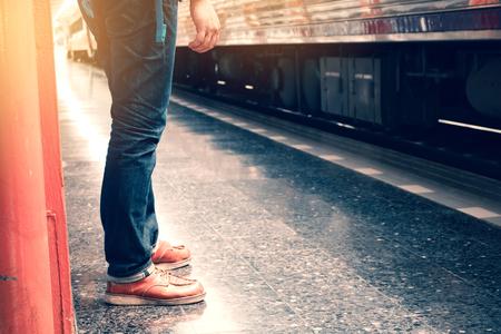 Young traveler asian man standing on platform waiting in train.