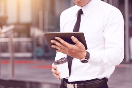 Morning time of young confident man economist holding digital tablet reading email or looking stock marketing.