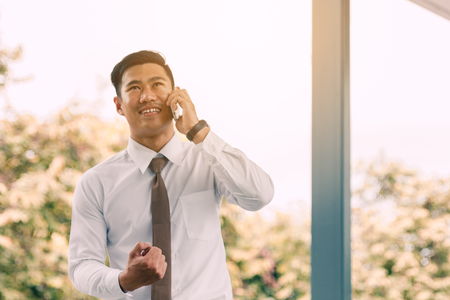 Young asian handsome businessman talking on phone and happiness for work.
