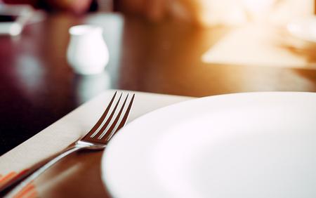 Solo tenedor cerca del plato en el escritorio en el restaurante.
