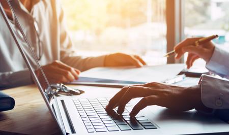 비즈니스 사람들이 또는 의사가 고객에게 이야기하고 Office 방에서 랩톱을 사용하는.