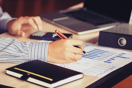 Mano de hombre de negocios que apunta al informe del resumen del gráfico y calcula la finanzas con la computadora portátil que busca la información de datos sobre el escritorio en la habitación de la oficina.