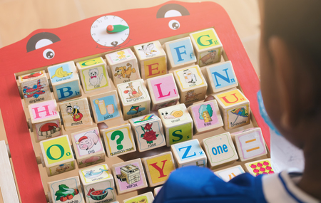 Asian boy looking and learning alphabet for english skill.