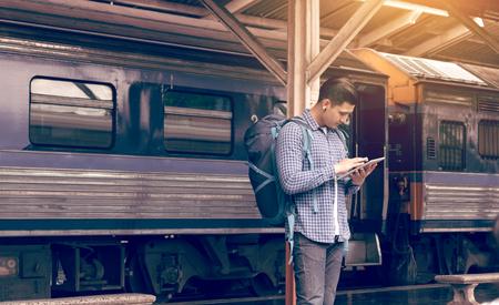 Asia hombre mochila para viajar en la estación de tren y el uso de la tableta buscando mapa de ubicación. Foto de archivo