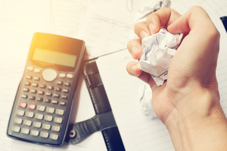 Businessman crumpled documents with frustrated hand expression. Foto de archivo
