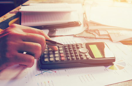 Hand man pressing on calculator with calculation about tax annual at home office. Foto de archivo