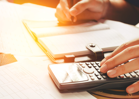 Business man accountant working at home  with using calculator and writing make note about savings concept.