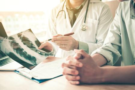 Doctor apuntando a la radiografía y describir una enfermedad viral o tumor a los pacientes.
