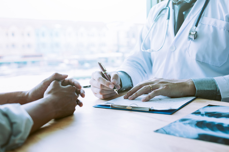 Asian male doctor hand holding pen writing patient history list on note pad.