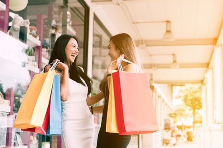 Happy two asian woman enjoying doing shopping together at the mall center.
