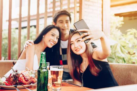 Grupo de amigos asiáticos sentados en el bar restaurante y tomando selfie con teléfono inteligente móvil.