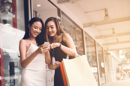 Two asian woman standing at store front with happy watching smart phone at shopping mall center. Фото со стока