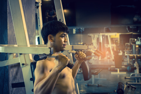 tough: Asian man pulling bar weight at indoor gym. Stock Photo
