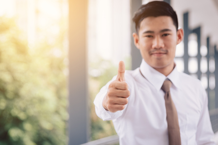 Business asian man shows thumb up.