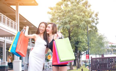 Dos amigos atractivos asiáticos de las chicas jóvenes en la calle al aire libre en la alameda de enchufe que ríe y que sonríe con los panieres.