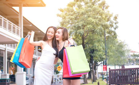 Two asian attractive young girls friends on the street outdoors at outlet mall laughing and smiling with shopping bags.
