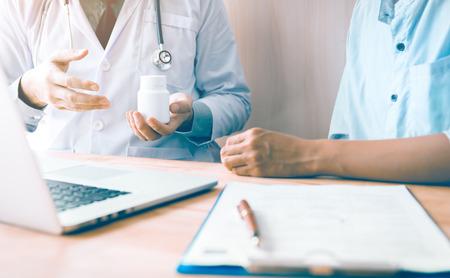 Hombre confiado del doctor que sostiene una botella de píldora mientras que habla con un paciente mayor y repasa su medicación en el cuarto de la oficina.