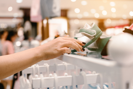 Woman hand holding baby shoe on shelve in shopping center.